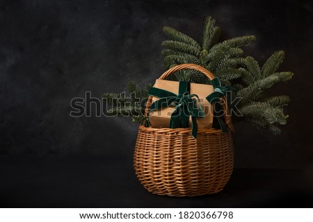 Christmas holiday gift hamper with craft gift and evergreen spice branches on black background. Xmas greeting card with copy space. Stockfoto ©
