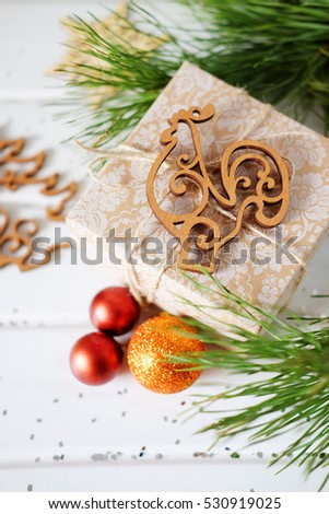 Christmas holiday gifts and wooden cutout new year tree rooster toys on white backdrop #530919025