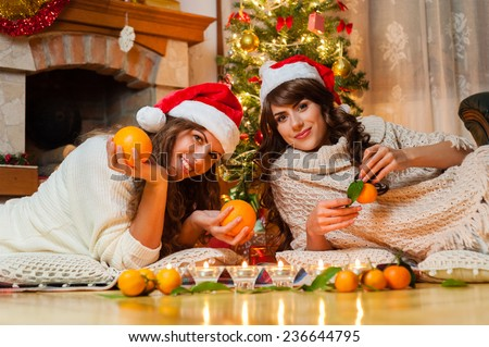 Christmas holiday happy girl friends playing with orange fruits , wearing red new year santa hat, over chimney and christmas tree colorful lights background. #236644795