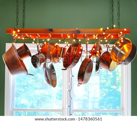 Christmas holiday lights decorate a ladder serving as a pot rack with copper pots hanging from its rungs