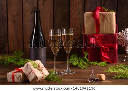 Christmas holiday table with glasses and a bottle of wine of champagne. Eve of new year, preparation and laying of a wooden holiday table