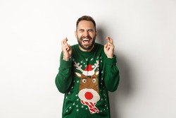 Christmas, holidays and celebration. Hopeful and excited guy making wish, keep fingers crossed for good luck and smiling, standing over white background