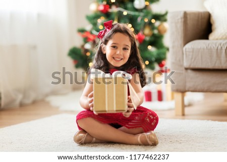 christmas, holidays and childhood concept - happy girl with gift box at home
