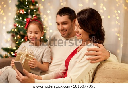 christmas, holidays and family concept - happy father, little daughter and mother with smartphone at home