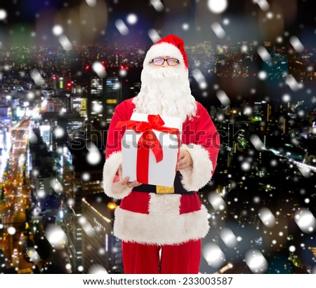 christmas, holidays and people concept - man in costume of santa claus with gift box over snowy night city background