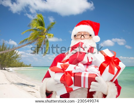 christmas, holidays and people concept - man in costume of santa claus with gift boxes over tropical beach background