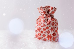Christmas holidays backdrop with gift bag, snow, bokeh and copy space for text. Christmas gift bag with red snowflakes.