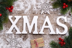 Christmas holidays background wooden letters pine tree branch covered with snow and decorations on old rustic surface