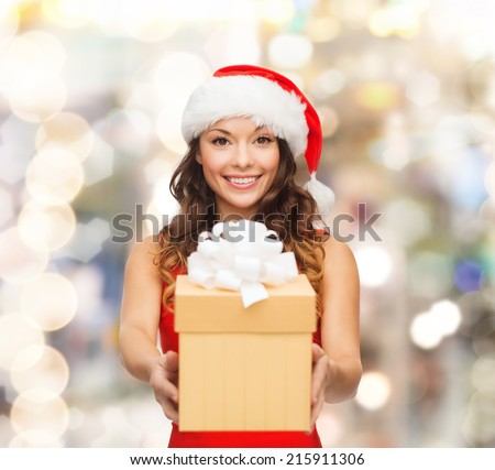 christmas, holidays, celebration and people concept - smiling woman in red dress with gift box over lights background