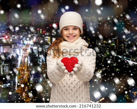 christmas, holidays, childhood, presents and people concept - dreaming girl in winter clothes with red heart over snowy night city background