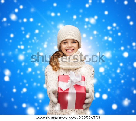 christmas, holidays, childhood, presents and people concept - dreaming girl in winter clothes with gift box over blue snowing background