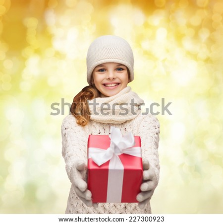 christmas, holidays, childhood, presents and people concept - dreaming girl in winter clothes with gift box over yellow lights background