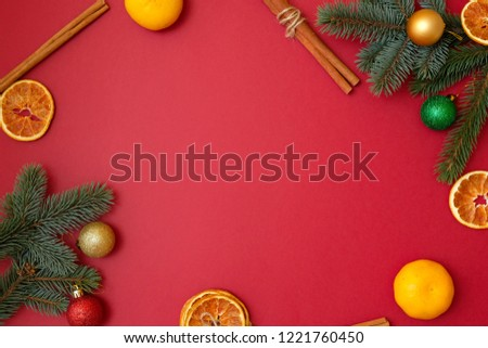 Christmas holidays composition on red background with copy space for your text. Xmas tree branches in the corners, dried oranges, cinnamon sticks. Xmas backdrop for greeting card. Flat lay, top view #1221760450