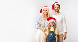 Christmas Holidays. Family Of Three In Santa Hats Standing And Smiling On White Background In Studio. Isolated