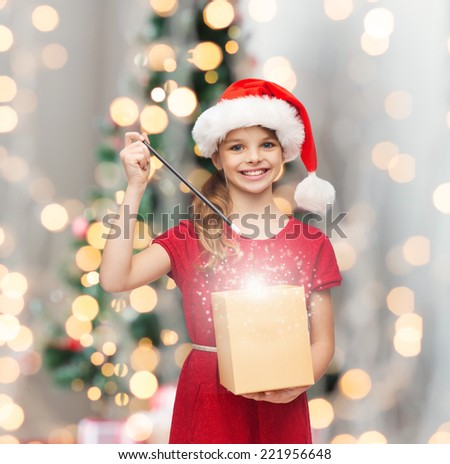 christmas, holidays, happiness and people concept - smiling girl in santa helper hat with gift box and magic wand over living room and christmas tree background