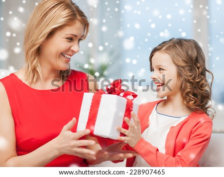 christmas, holidays, people and family concept - smiling girl receiving gift box from mother at home