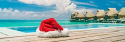 Christmas holidays summer travel tropical destination vacation at luxury resort hotel. Banner santa claus red hat on swimming pool holiday horizontal panorama for south holidays winter vacations.