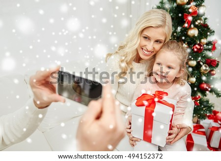 christmas, holidays, technology and people concept - happy family sitting on sofa and taking picture with smartphone at home