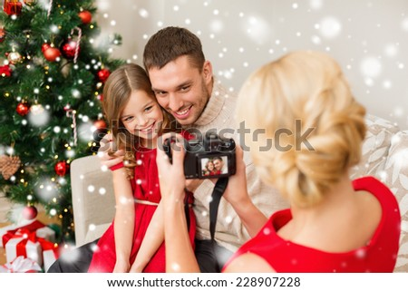 christmas, holidays, technology and people concept - happy family with digital camera taking photo at home