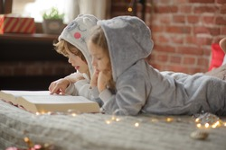 Christmas Holidays. Two children, brother and sister lie on big bed and read Christmas tales. Children dressed in fluffy pajamas, like little cute animals. Before them the huge book. Magic Christmas.