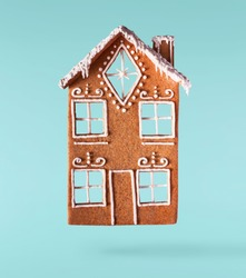 Christmas holliday card. Flying in the air gingerbread house  isolated on the turquoise background. Merry christmas levitation concept. High resolution image.