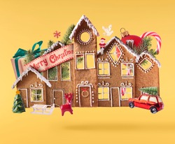 Christmas holliday card. Flying in the air gingerbread houses with christmas decorations isolated on the yellow background. Merry christmas levitation concept. High resolution image.