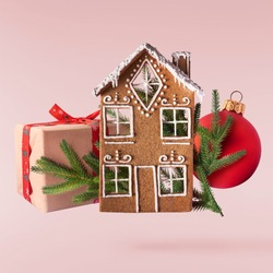 Christmas holliday card. Flying in the air gingerbread houses with christmas decorations isolated on the pink background. Merry christmas levitation concept. High resolution image.