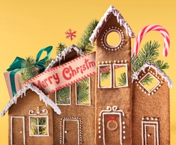 Christmas holliday card. gingerbread houses with christmas decorations isolated on the yellow background. Merry christmas concept. High resolution image.