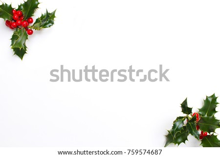 Christmas holly decoration on white background. Evergreen leaves with red berries and empty space for holiday text. Styled stock photo, top view. #759574687