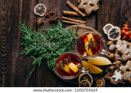 Christmas home atmosphere. Cozy and warming winter drink. Hot mulled wine, delightful festive sweets and spices on rustic wooden background, flat lay