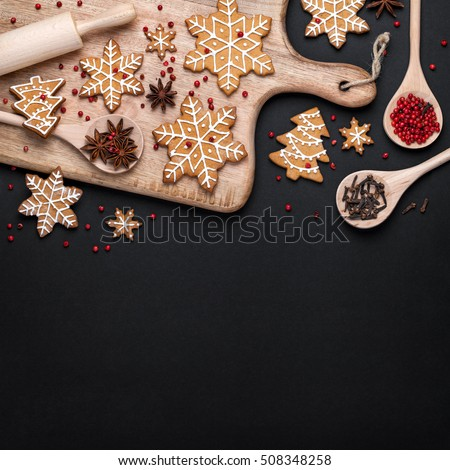 christmas homemade gingerbread cookies, spices and cutting board on black background with copy space for text top view. holiday, celebration and cooking concept. new year and christmas postcard