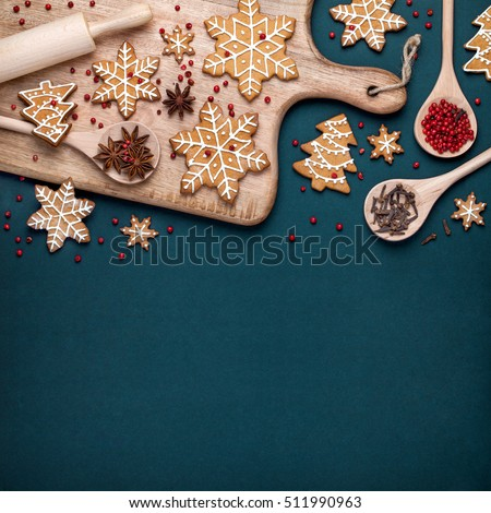 christmas homemade gingerbread cookies, spices and cutting board on dark green background with copy space for text top view. holiday, celebration and cooking concept. new year and christmas postcard