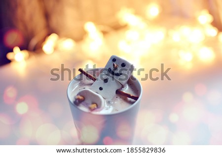 Christmas hot chocolate with fun marshmallow snowman in red cup in bokeh light background. White mug with hot chocolate or coffe with melted marshmallow snowman.  snowmen soaking in a hot mug.