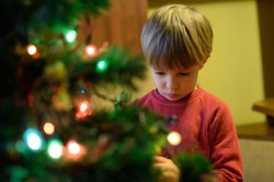 Christmas in a poor home. The child decorates the Christmas tree. Poor family, poor child. Preparations for Christmas in a poor family.