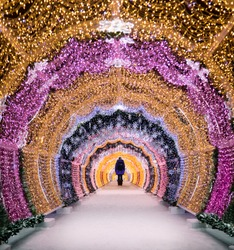 Christmas in  Moscow Russia. The light tunnel at Tverskoy Boulevard Tverskaya Street. New Year decorations beautiful magical lights. Silhouette of a woman in the end of the tunnel