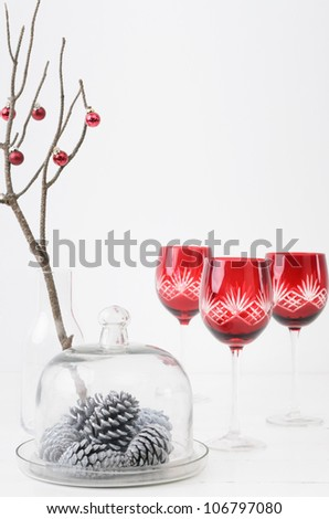 Christmas interior decorating minimalist elegant style, silver white pine cones in glass dome with festive red wine glasses