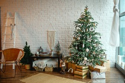 Christmas interior in the style of a Scandinavian loft: gray concrete, wooden decor, incandescent lamps, realistic artificial Christmas tree. Cozy new year in a country house
