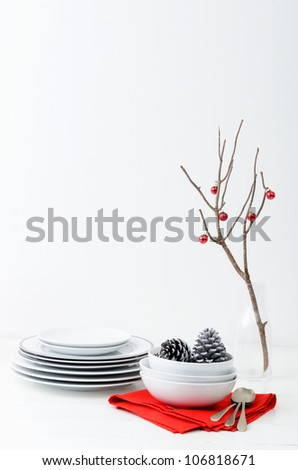 Christmas interior table decoration in simple, minimalist, elegant style with bare branch and red baubles, plenty of copy space