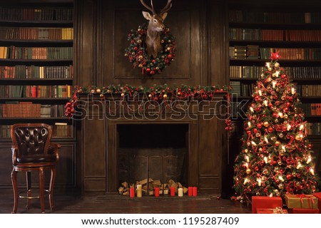 Christmas interior with bookshelves, stuffed deer, wooden fake fireplace, christmas tree, boxes, chair in studio