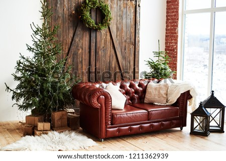 Christmas interior with vintage brown leather sofa and fir tree with gift boxes in loft room with wooden door and panoramic window, copy space