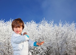 Christmas is coming. Frosty snowy sunny day in the winter forest. Deep snow covered the ground. Handsome boy in judo uniform. Judo is a humane modern martial art.