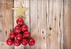 Christmas jingle bells and golden star shaped like a Christmas tree on a rustic wooden plank