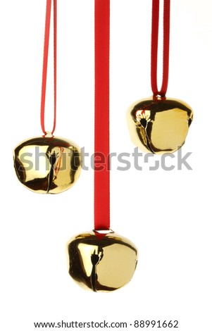 Christmas jingle bells hanging on red ribbon, isolated on white
