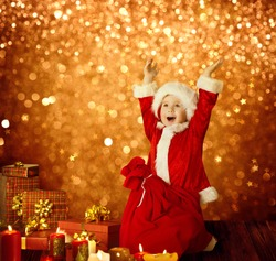 Christmas Kid, Happy Child Presents Gifts and Red Santa Bag, Boy Arms up, Golden Xmas Lights