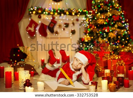 Christmas Kid Write Wish List, Child in Santa Claus Hat Writing Letter, Boy in Holiday Room lying under Christmas Tree