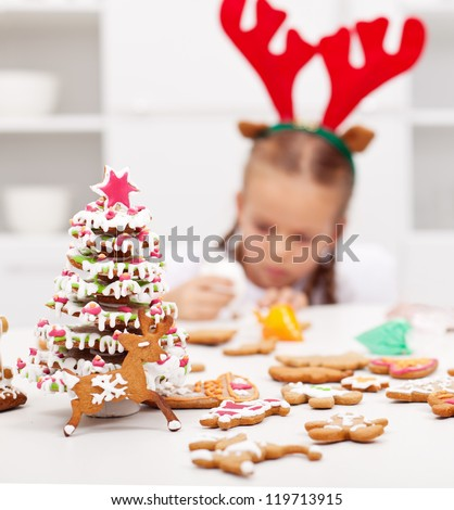 Christmas kids dressed as reindeer  decorating gingerbread cookies - focus on foreground