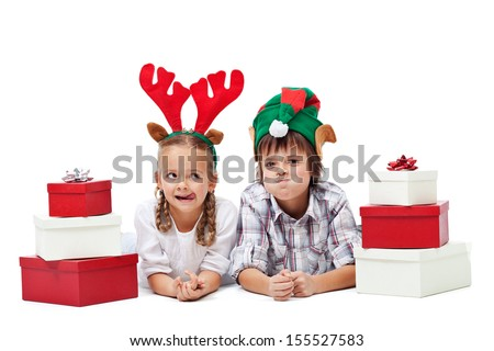 Christmas kids with presents and funny hats making faces - isolated
