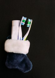 Christmas kit from the dentist. Blue sock with two toothbrushes and a tube of toothpaste on a black background.