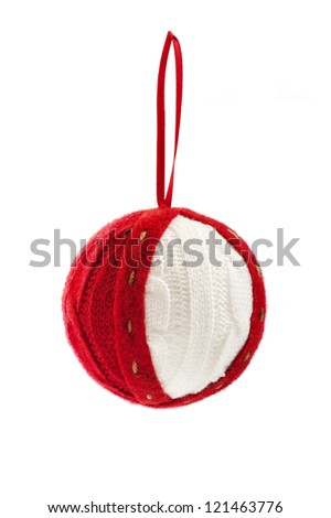 Christmas knitted ball hanging on red ribbon close-up isolated on white background