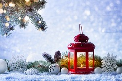 Christmas lantern in snow with fir tree branch and holiday decorations. Winter cozy scene.